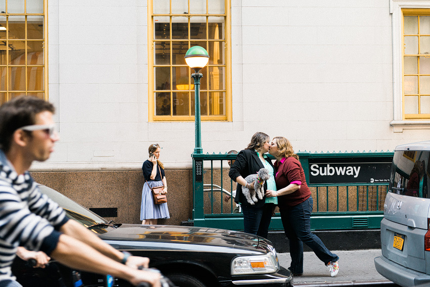 lesbian couple kissing in front of new york subway