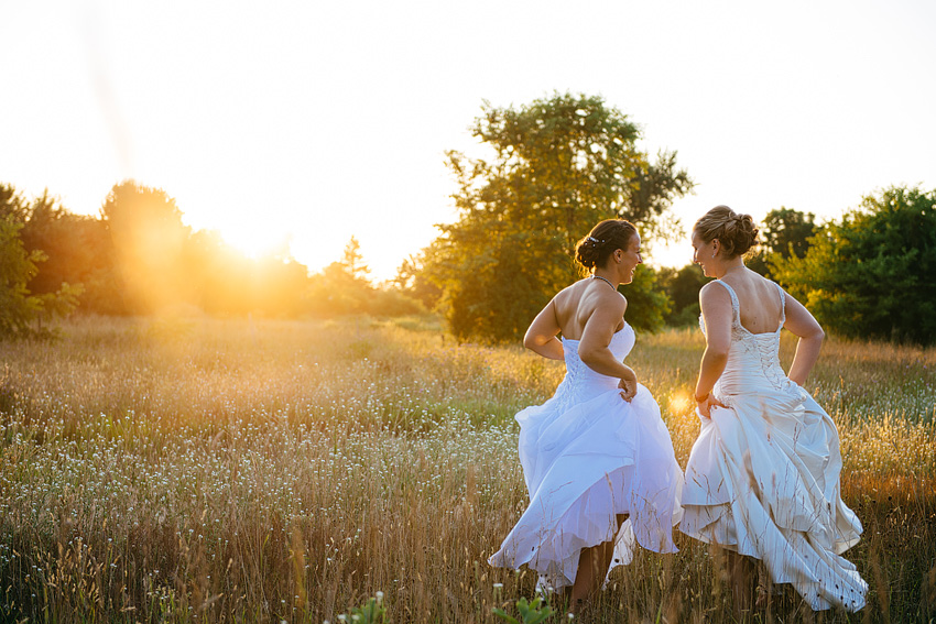 two brides dancing in field with wedding dresses