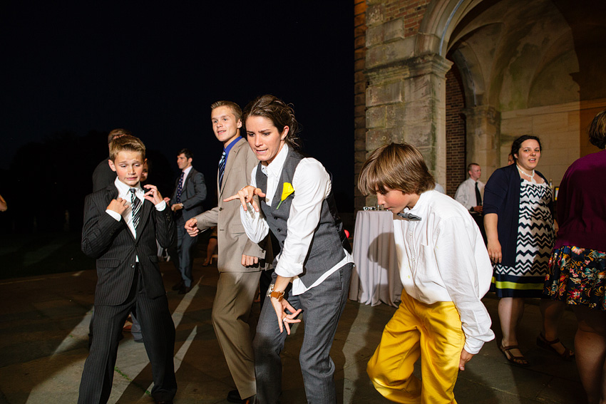 bride in suit dancing with kids at reception
