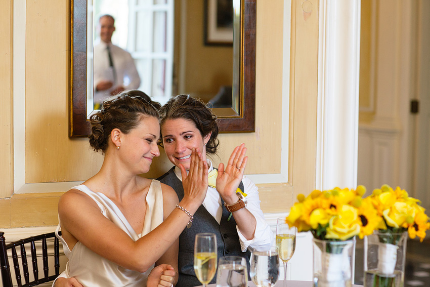 brides high fiving at table with champagne