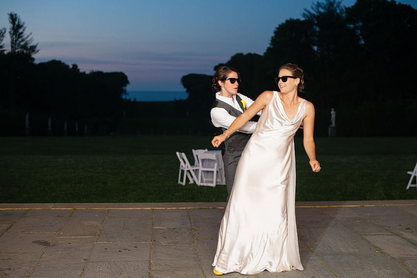lesbian couple dancing in sunglasses at wedding reception