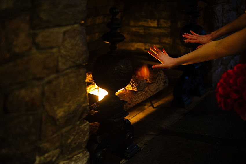 warming hands by fireplace
