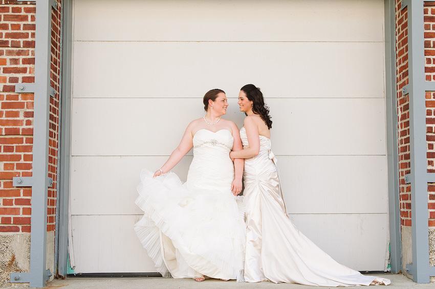 two brides posing in front of garage door
