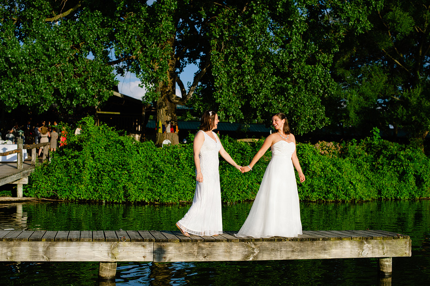 two brides holding hands on dock