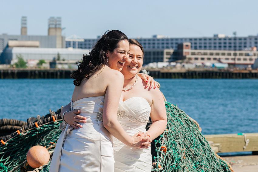 brides hugging at waterfront
