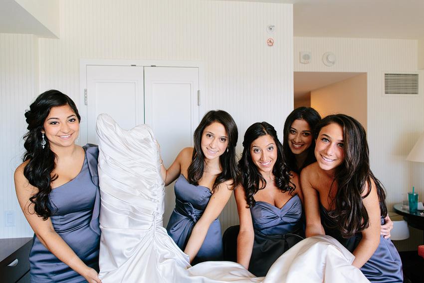 bridesmaids holding up wedding dress