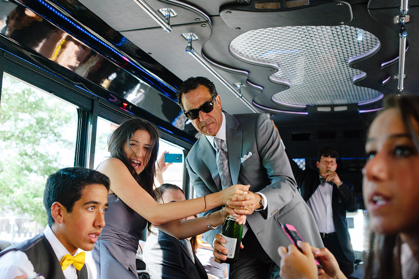 wedding party popping champagne in limo