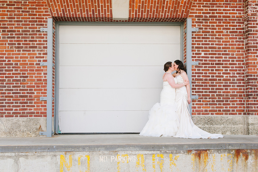 brides kissing in front of loading garage