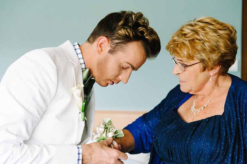 groom placing corsage on mother