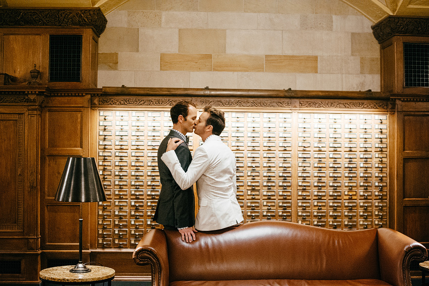 grooms kissing in front of mailboxes