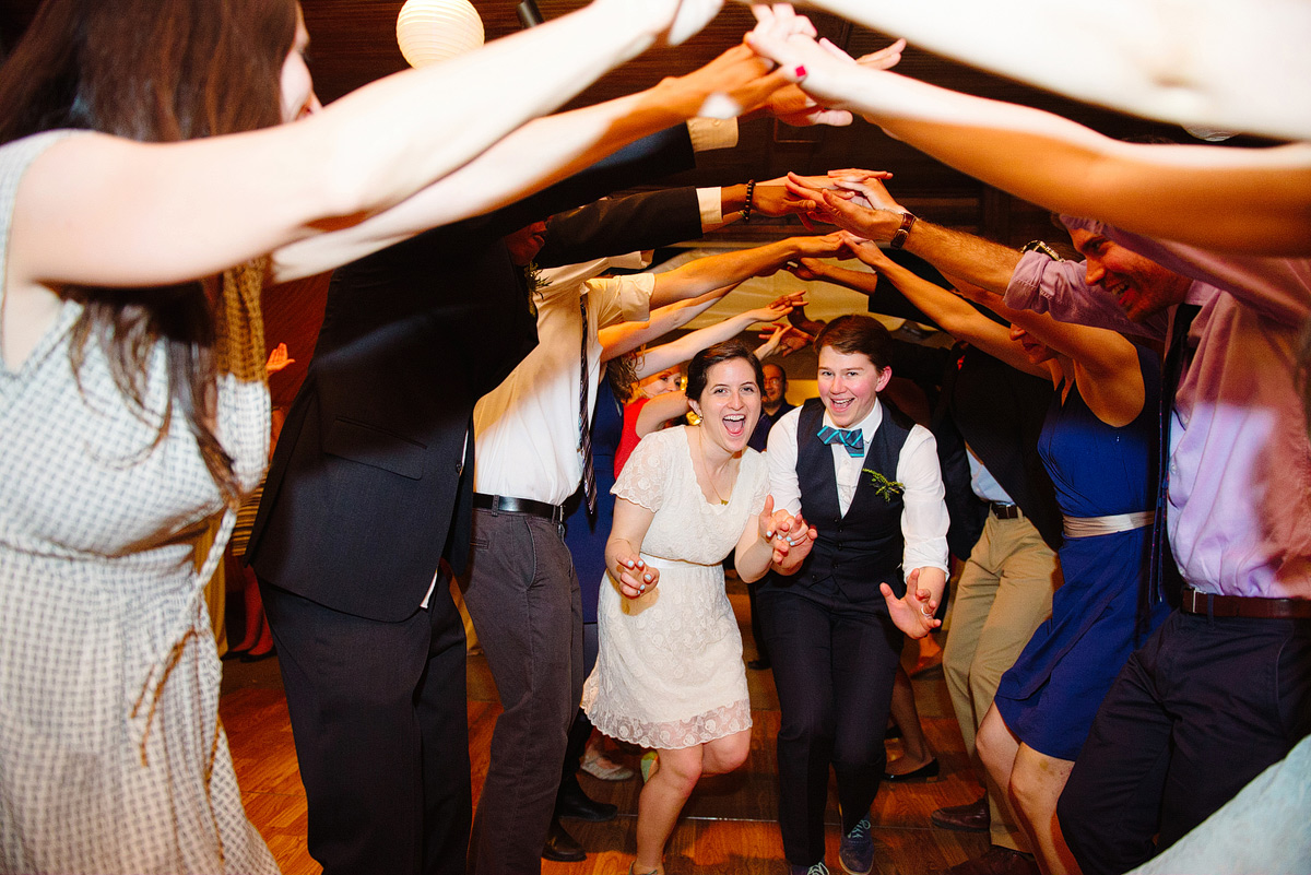 couple runs under wedding party's arms