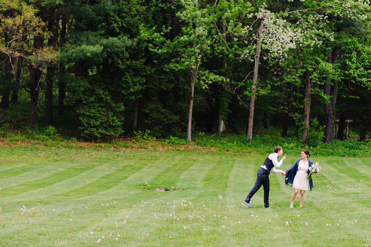 couple runs through field at codman estate wedding venue