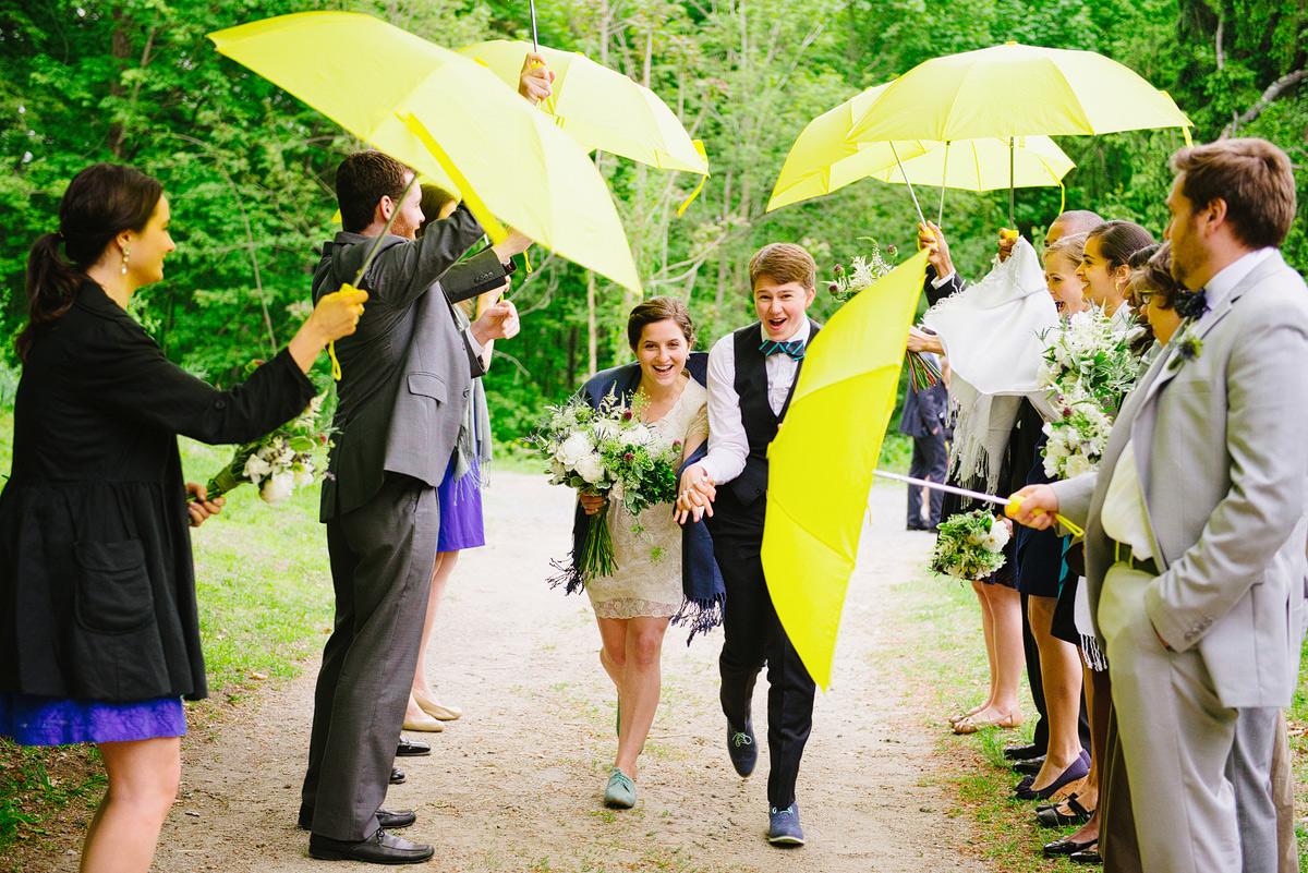 couple runs under umbrellas on rainy wedding day