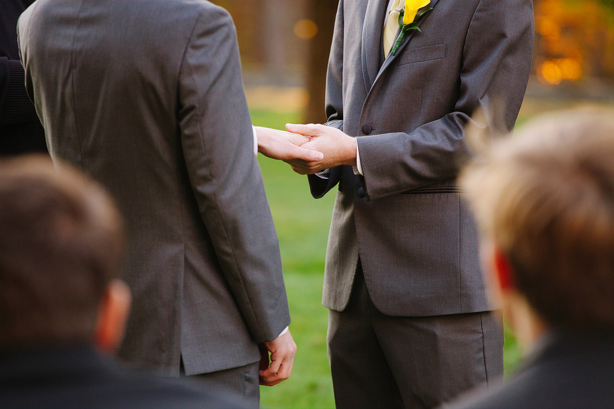 grooms hold each others hands