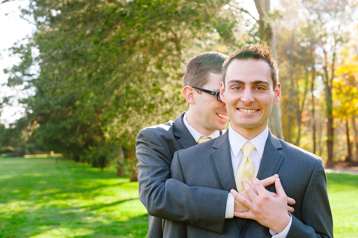 grooms hug in field