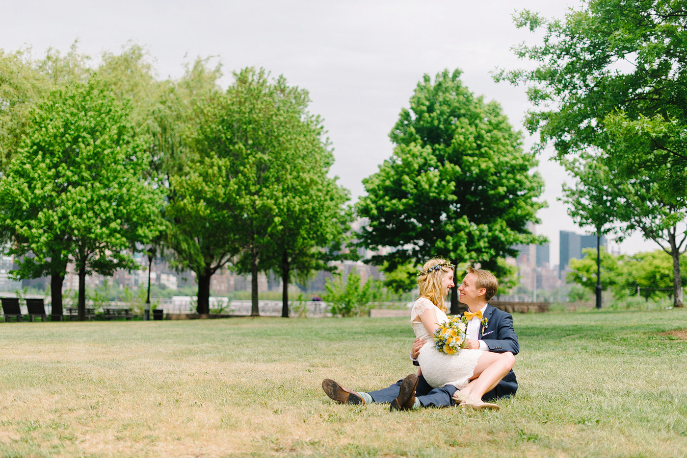 couple cuddling in new york park on wedding day