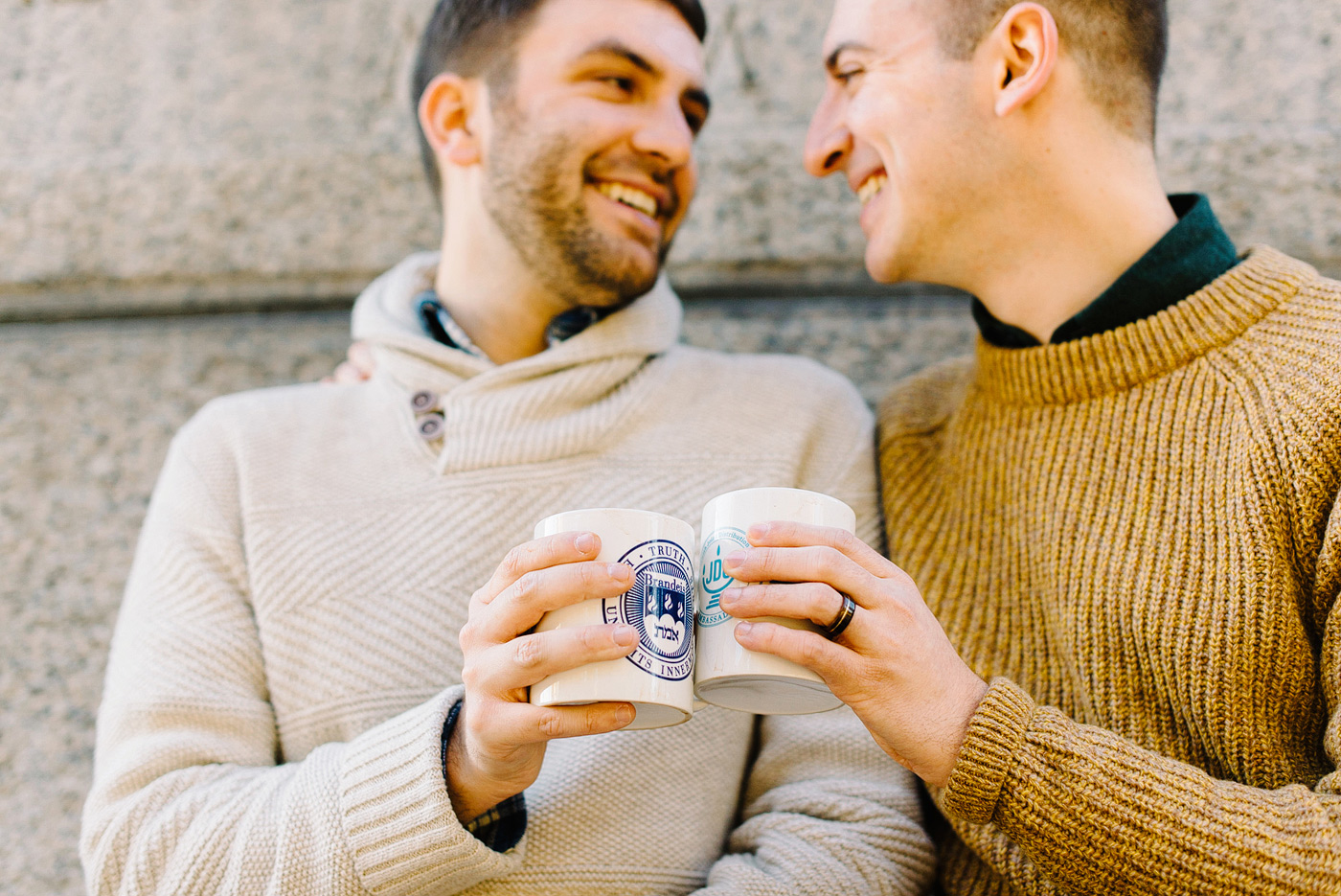 couple clinking mugs in fall sweaters